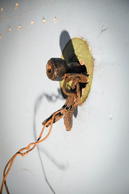 I am assuming this is an old gas fixture for the master bedroom.  I ended up getting rid of the wire and removing the bolt, but just leaving the protruding pipe.